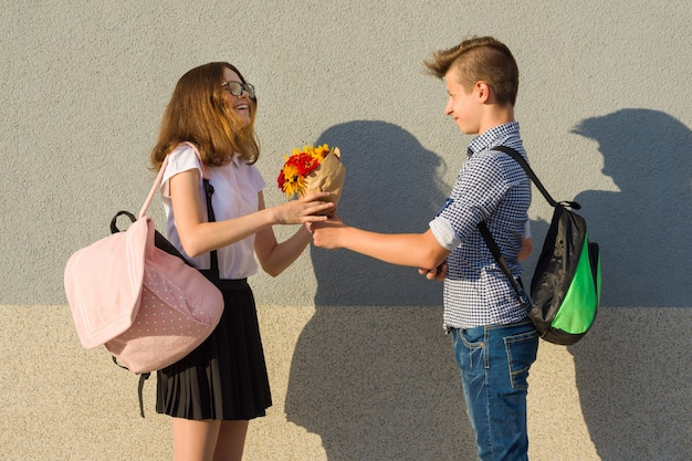 Boy gives girl bouquet of flowers