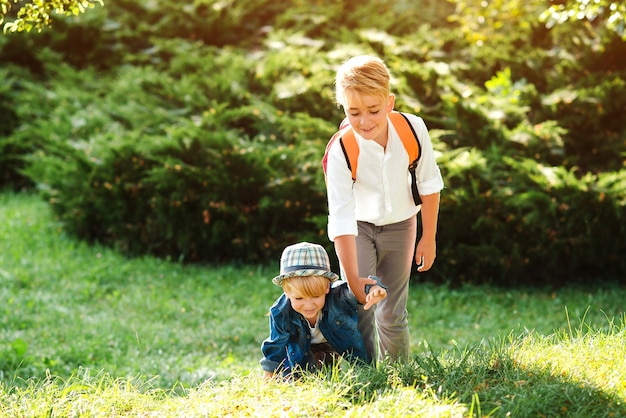 Boy gives hand to his little brother on a walk. school boy helps to stand up his friend. children help and support each other. children walking together in summer park. happy brothers outdoors.