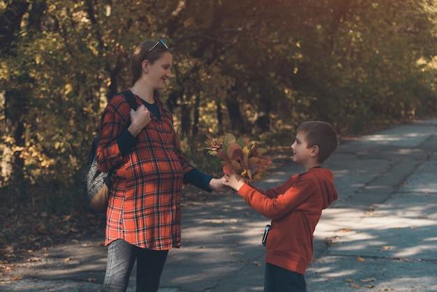 Мальчик дарит беременной маме букет из желтых листьев. осенний парк на заднем плане