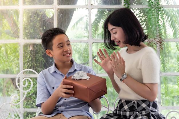 誕生日、クリスマス、新年のプレゼントの女の子にギフトボックスを与えるボーイ