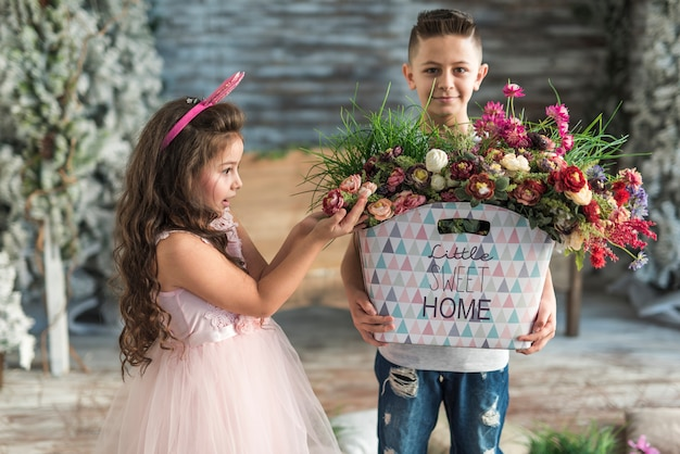 Boy giving bag with flowers to amazed girl in bunny ears