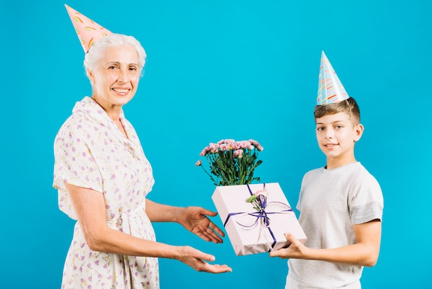 Boy giving birthday gift and flowers to happy grandmother on blue backdrop