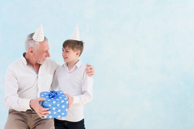 Boy giving blue gift box to his grandfather on his birthday