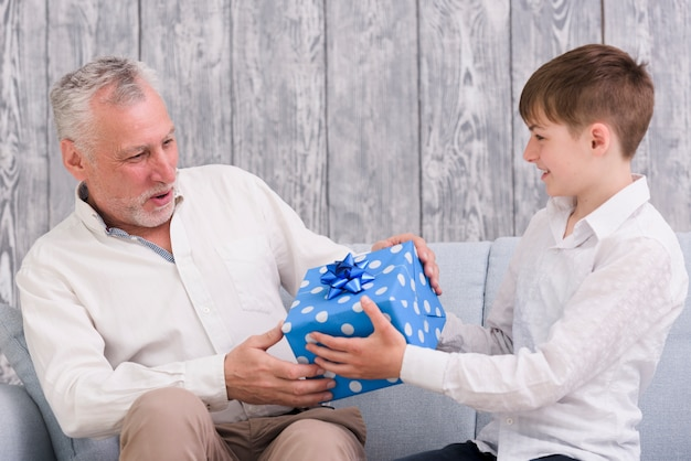 Boy giving blue wrapped birthday gift box to his grandfather