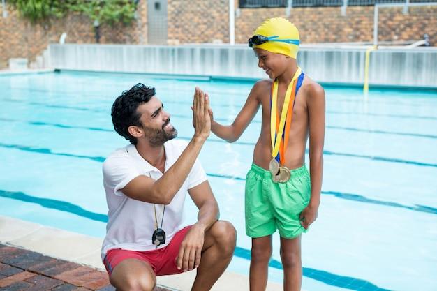 レジャーセンターのプールサイド近くのコーチにハイタッチをする少年