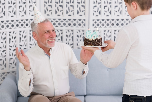 Boy giving surprised birthday cake to his happy grandfather sitting on sofa
