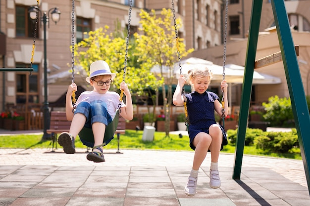 Boy in the glasses and hat and blonde girl in the dress having fun on a swing together in beautiful summer garden.