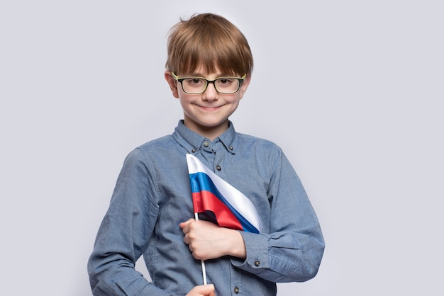Boy in glasses holding flag of russia on white