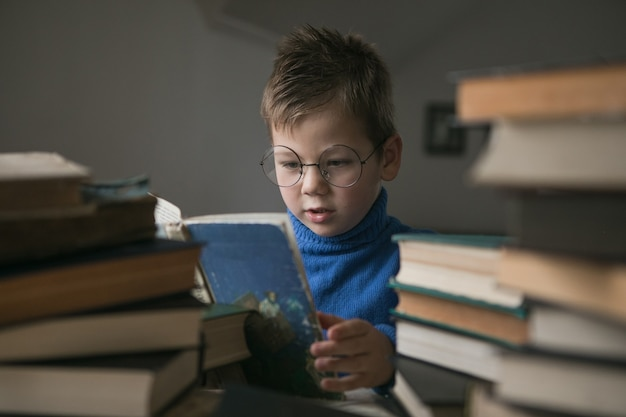 Boy in glasses reading a book with a stack of books next to him.