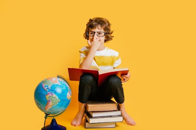 Boy in glasses  sits on a stack of books, near to the globus