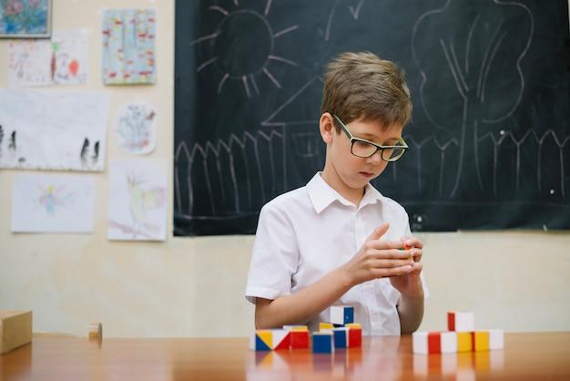 Ragazzo in bicchieri che risolve il puzzle