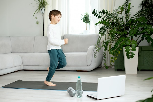 The boy goes in for sports at home online. the child does exercises in the room.
