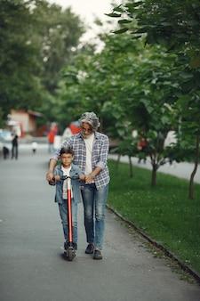 Il ragazzo e il nonno stanno camminando nel parco. uomo anziano che gioca con il nipote. bambino con scooter.