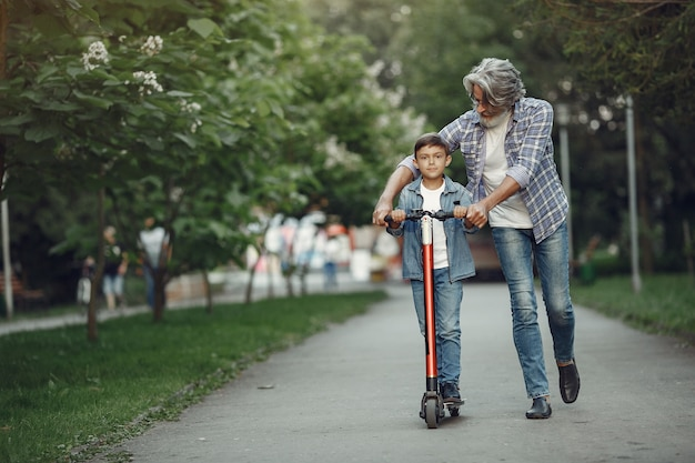 Boy and grandfather are walking in the park. old man playing with grandson. child with scooter.