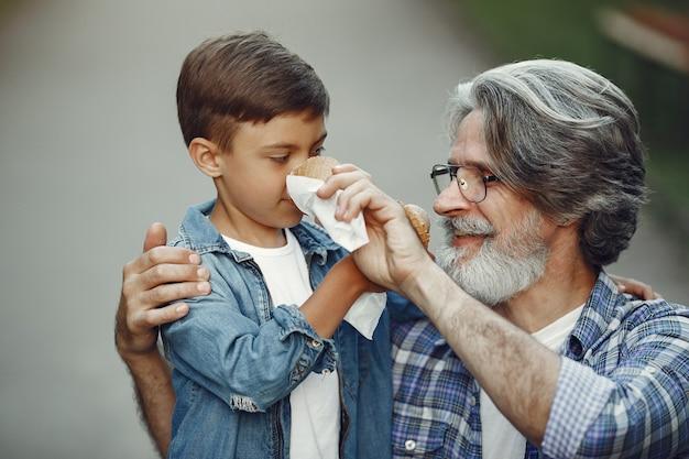 Il ragazzo e il nonno stanno camminando nel parco. uomo anziano che gioca con il nipote. famiglia con gelato.
