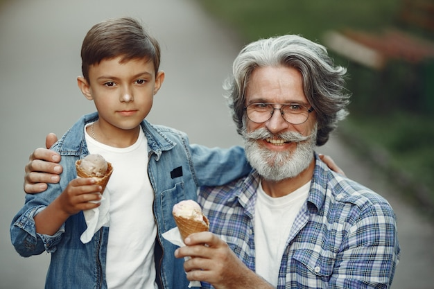 Boy and grandfather are walking in the park. old man playing with grandson. family with ice cream.
