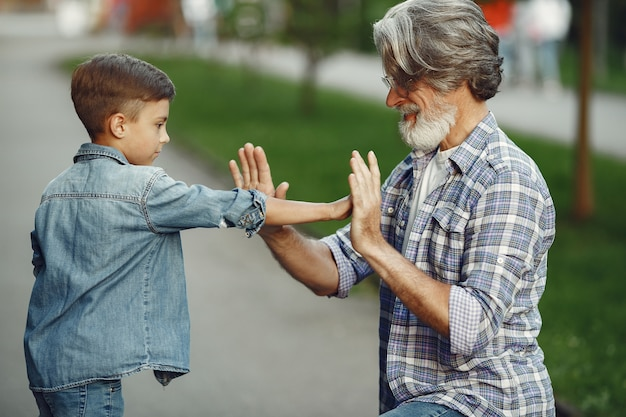 Boy and grandfather are walking in the park. old man playing with grandson.