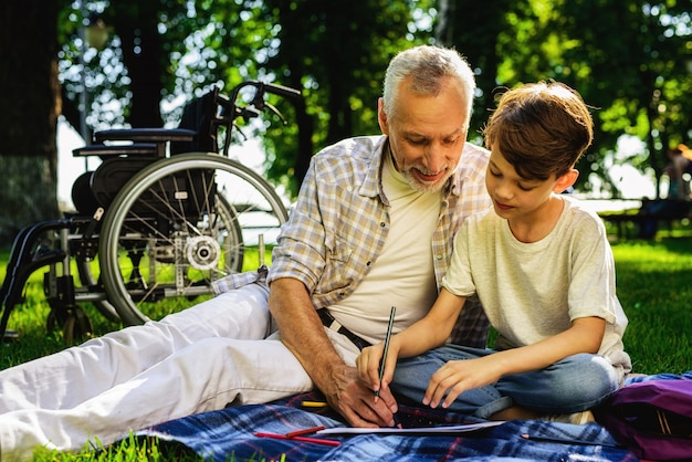 Boy and grandfather draw notbook family picnic