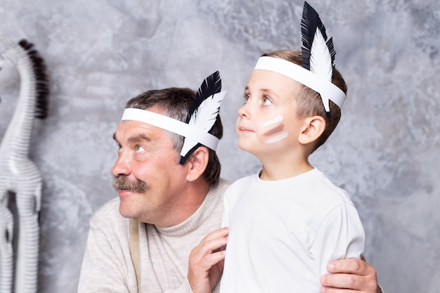 Boy and grandfather play indians on a gray wall wall. senior man and grandson play injun. portrait close-up
