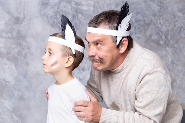Boy and grandfather play indians on a gray wall wall. senior man and grandson play injun