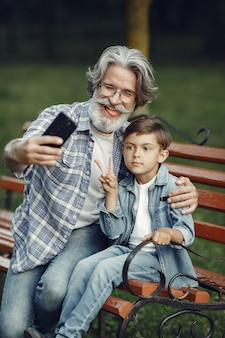Boy and grandfather sitting on a bench. family in the park. old man playing with grandson. grandfather use a phone.