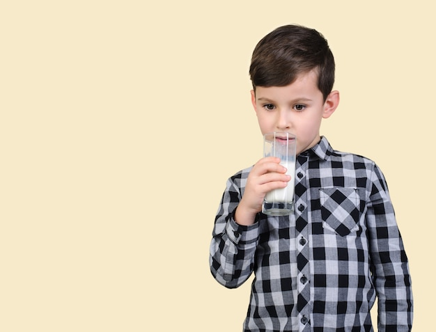 Boy in a gray shirt drinks milk on a light background