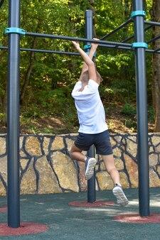 屋外の少年体操。遊び場の鉄棒に小さなスポーツマン