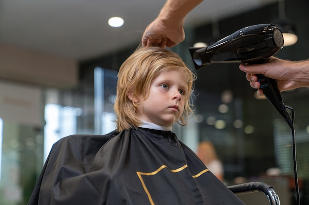 A boy in a hairdresser's stylist dries his hair with a hairdryer after a haircut