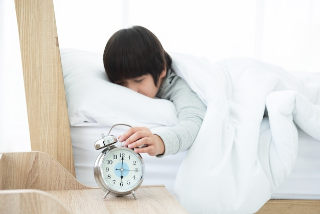 침대에 누워있는 동안 아침에 알람 시계를 위해 밖으로 도달하는 소년 손