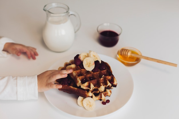 Boy hand touching waffle