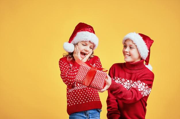 Boy handing christmas present to surprised girl