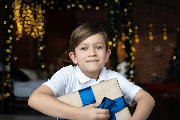 男の子の手は、クリスマスプレゼントや新年の装飾が施されたギフトボックスを保持します。喜び平和愛