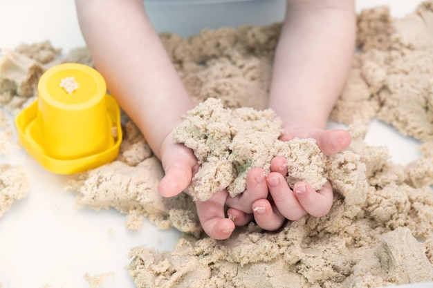 Boy hands playing with kinetic sand at home. early age education. toddler playing.