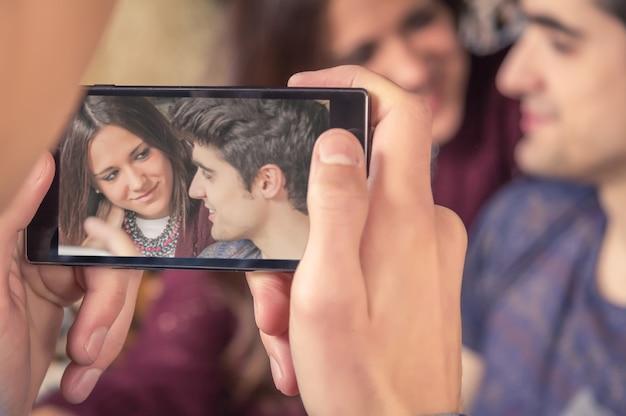 Мальчик руки фотографирует подростковую пару на диване