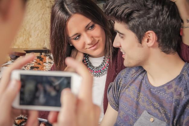 ソファで10代のカップルに写真を撮る少年の手