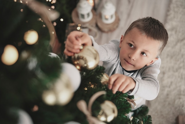 크리스마스 트리에 크리스마스 장식품을 거는 소년