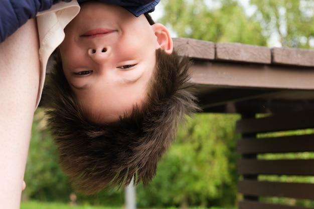 男の子は母親の足でベンチから逆さまにぶら下がっています子供のいたずらについての面白い写真