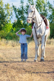 The boy in a hat costs near a white horse