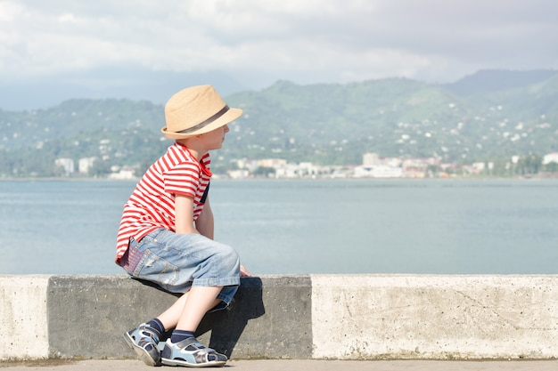 Boy in a hat and striped t-shirt sitting on the beach and looks at the sea. side view