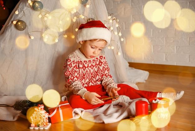 Мальчик, имеющий рождественский видеозвонок с маленьким ребенком санта-клаусом