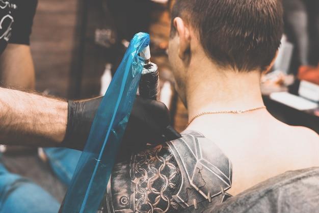 Мальчик делает татуировку