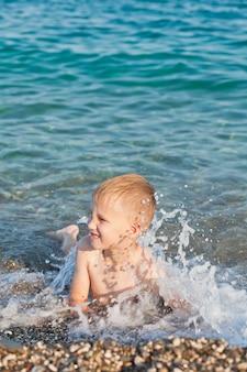 夏の晴れた日に海や海の波で楽しんでいる少年。海の海岸とビーチ。アクティブなライフスタイルとレクリエーションの概念。
