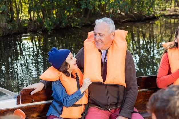 ボートに乗って彼の祖父との楽しみを持つ少年