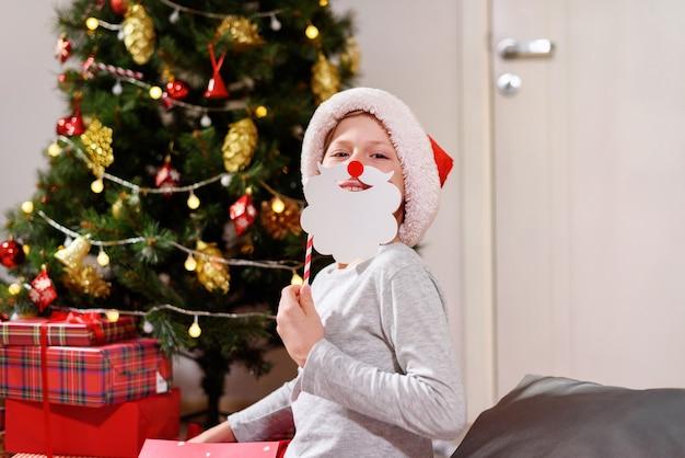 Мальчик с удовольствием носит праздничный декор, используя онлайн-общение с помощью ноутбука. дистанционная рождественская вечеринка. социальное дистанцирование