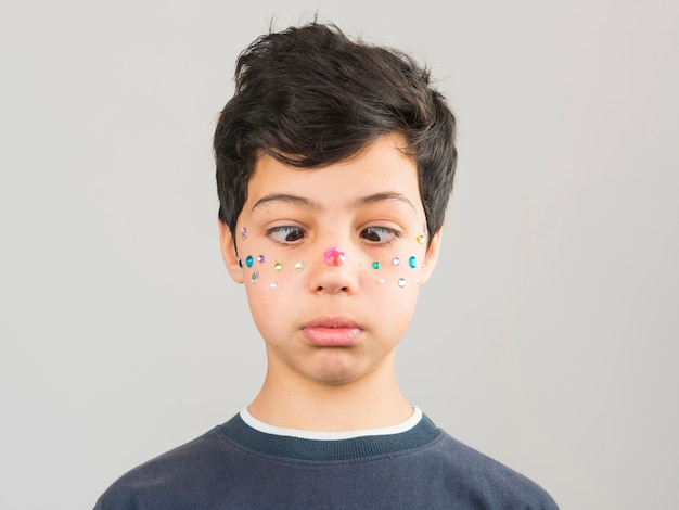 Boy having make-up pearls on his face