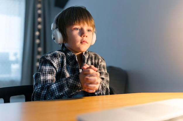 노트북에 가상 과정을 가지고기도하는 소년