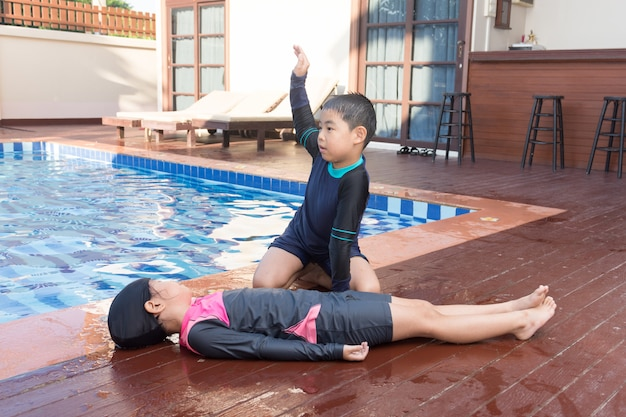 Boy helping drowning child girl in swimming pool by doing cpr.