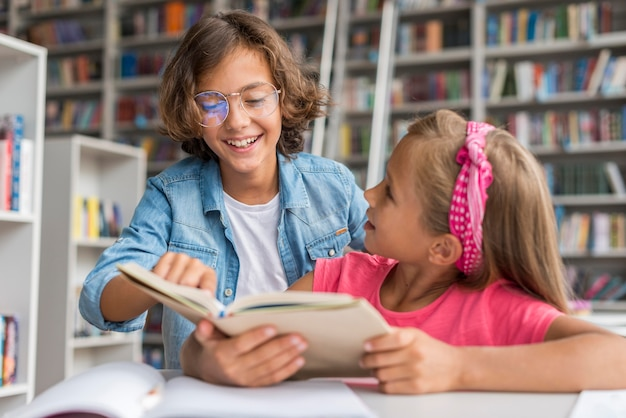 Мальчик помогает своему коллеге делать домашнее задание в библиотеке