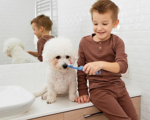 Мальчик помогает своей собаке мыть зубы дома