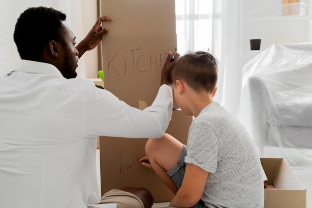 Ragazzo che aiuta suo padre a trasferirsi